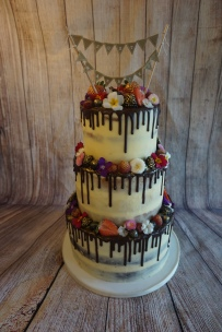 3 tier semi-naked cake with drip, edible flowers and fresh fruit