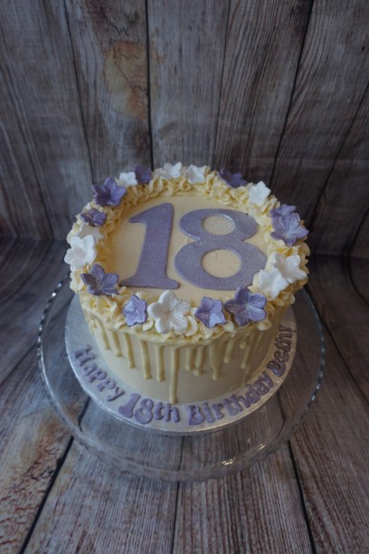 White chocolate drip cake with flowers, large age numbers and message on board-