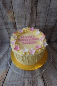 White chocolate drip cake with flower details and message