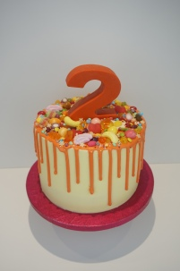 Orange themed drip cake with chocolate number and rainbow sweets
