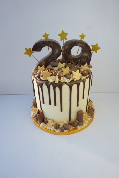 Loaded chocolate cake with gold numbers and gold stars
