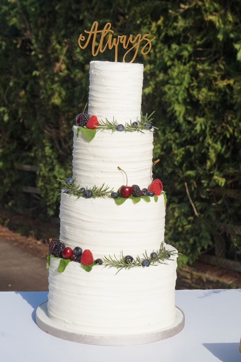 4 tier rustic buttercream cake with thyme and fruit decoration