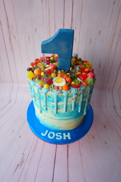 Blue themed drip cake with chocolate number and rainbow sweets