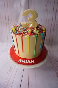 Rainbow drip cake with rainbow sweets and chocolate number